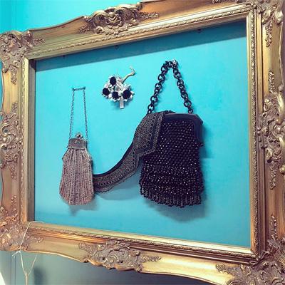 ターコイスの壁面に、アンティークゴールドのフレームとモノトーンのバッグ