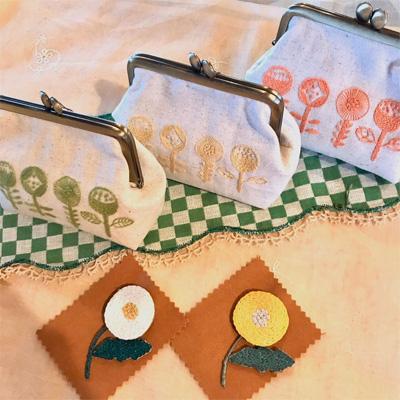 糸とも さんの刺しゅうがま口ポーチとお揃いのデザインのブローチ