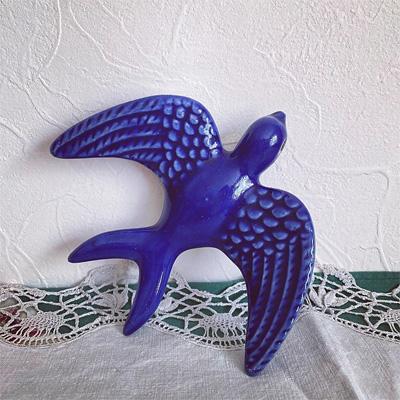 るり色の羽根を広げて飛ぶツバメ