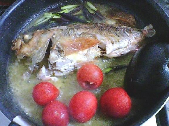 魚に火が通ったらトマトとアスパラを入れます