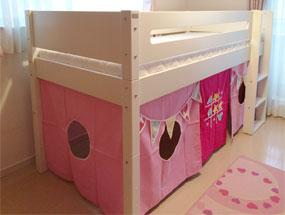 ピンクのカーテンが引き立つミドルベッド