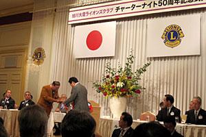 50周年記念アクティビティの目録を贈呈するL高橋(左)と西川将人旭川市長