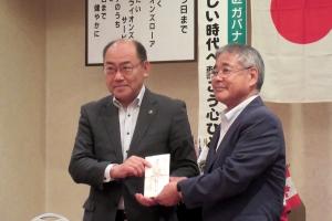例会で士別愛成会の小笠原氏(右)にイベント基金を贈呈する松ケ平会長(左)