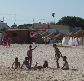 地元のビーチで遊ぶチュニジア人の子供たち