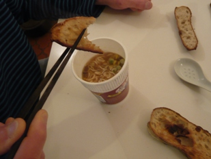 出前一丁にバゲットをつけて食べるフランス人の写真