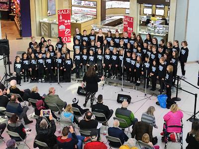 ショッピングセンターでクリスマスキャロルを歌う小学生