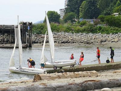 海からヨットを引き上げる子供たち