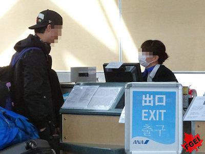 空港のカウンターで帰国手続きをする留学生
