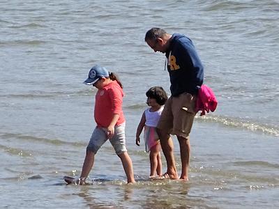 海に足をつける親子連れ
