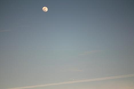夕暮れの飛行機雲と月