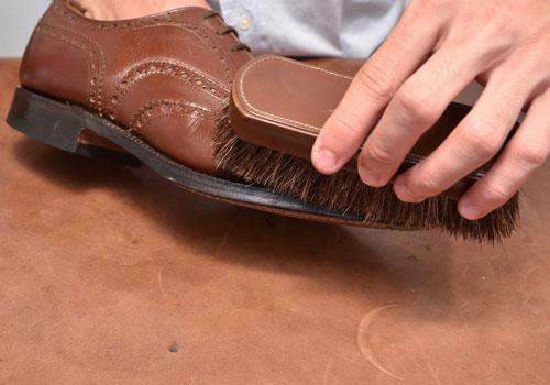 馬毛ブラシで革靴をブラッシングしている