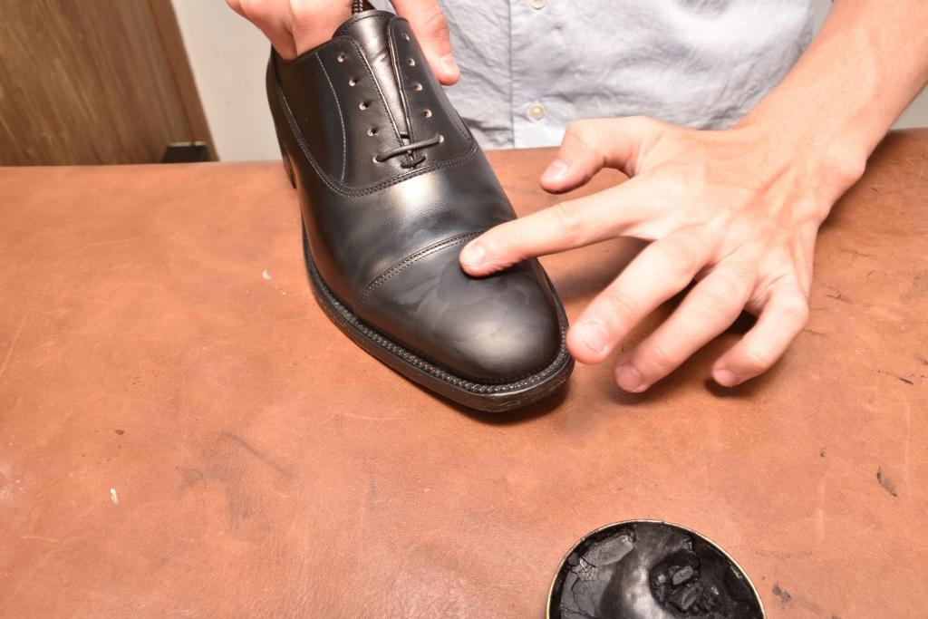 革靴のつま先にワックスを塗布している様子