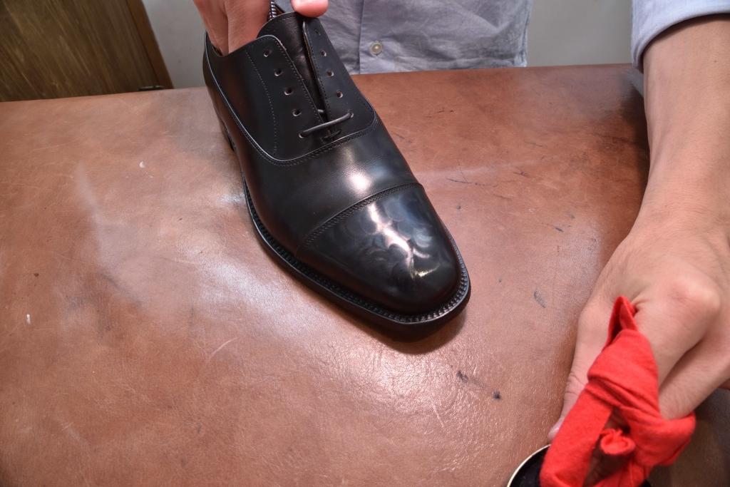 革靴のつま先にワックスの膜を張っている様子
