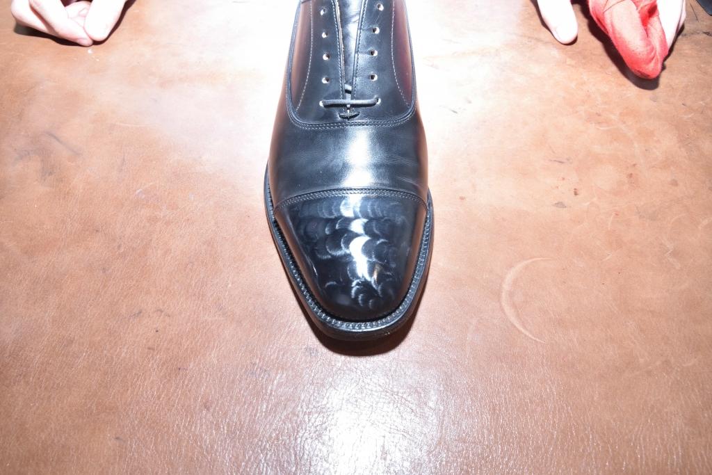 革靴のつま先部分にワックスの膜を出している様子