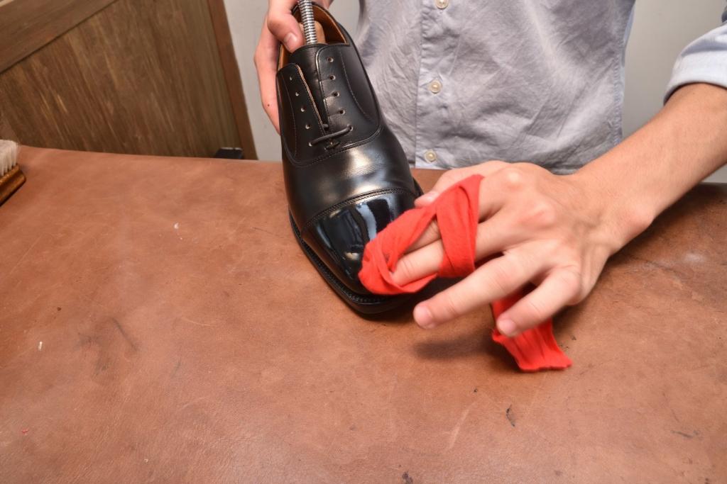 革靴のつま先部分にワックスの膜を出している2