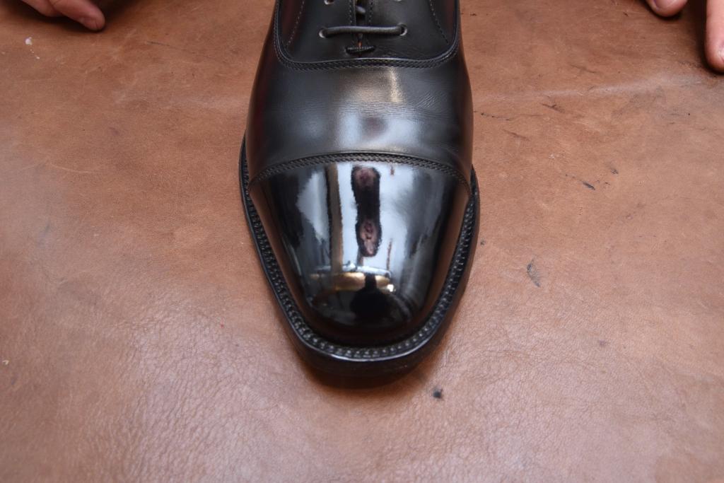 革靴のつま先部分に顔が映っている様子