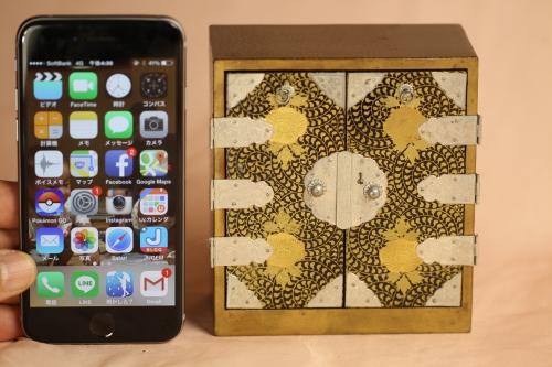 昭和の雛道具とiPhoneを比べています。
