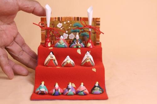 お内裏様などをのせた三段飾りのお雛様です。大きさは幅10cm、奥行き20cm、高さが13cm程度です。