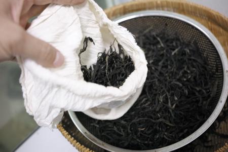 蒸して熱々の茶葉を手で袋に詰める