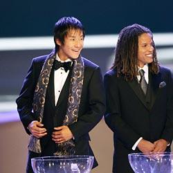 1次リーグの組み合わせ抽選会で、笑顔を見せる元日本代表の中山雅史選手(左)。右は元米国代表のコビ・ジョーンズ氏