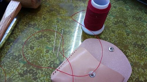 革を蝋引きの糸で縫う
