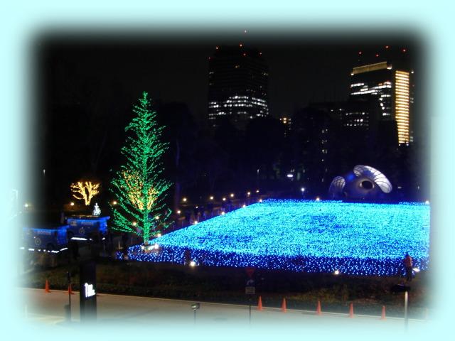 東京ミッドタウンの夜のイルミネーション。正面の背景は、六本木ヒルズ