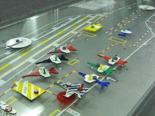 飛行管制センターのコントロール・ボードで、正確な縮尺の艦載機の模型によって管制をしている。緑のピンは最初に発艦する機、黄色はその次に発艦する機を示すなど、付けられている飾りにはひとつひとつ意味がある。丸くて白いのはヘリコプターを示す。ちなみに、故障するとひっくり返す。