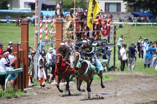 甲冑競馬で勝って手を挙げる武者