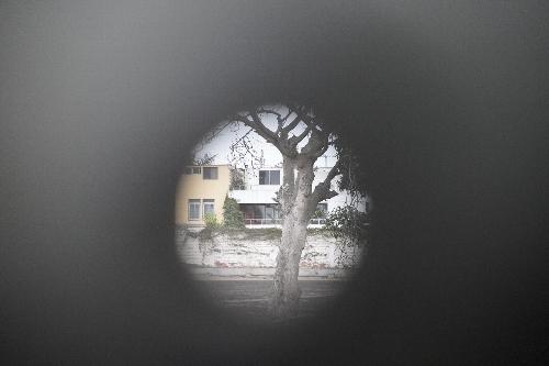 旧日本大使公邸跡の門の扉に空いたままとなっている銃弾による穴から中を眺める