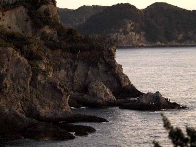 崖の下の岩の上の釣り人