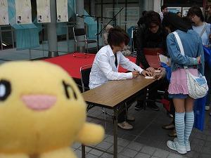サインを書いている樋口さん