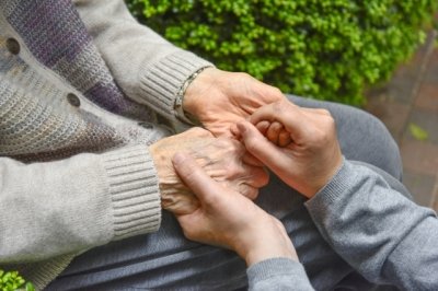 高齢者の手を握る介護職