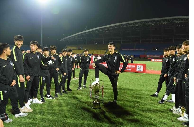 優勝トロフィーフィーを踏みつける韓国選手