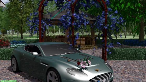 アストンマーチンとクレマチスのアーチと東屋のあるバラ庭園