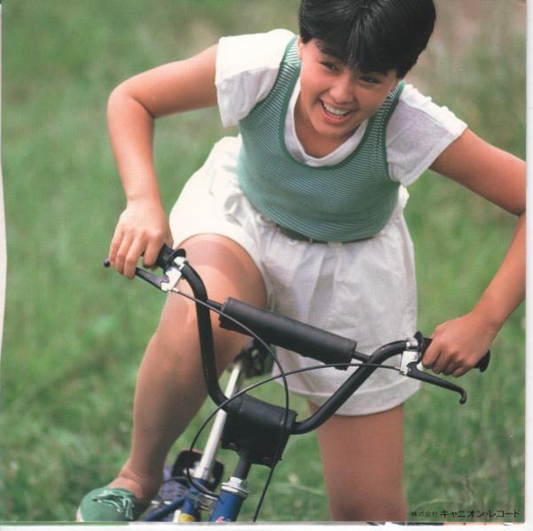 自転車に力強く乗る元気いっぱいの笑顔の井森美幸