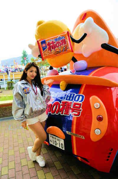 キャンペーンカー「亀田の柿の種号」のリア部分とイメージキャラクター村架純さんに似ているキャンペーンスタッフの画像