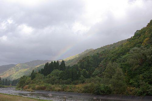 雨が降ったりやんだり。紅葉の始まった山に虹。