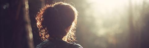森の中で佇み日差しを見つめる女性の姿