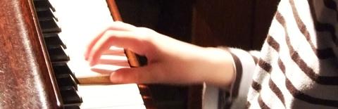ピアノ鍵盤上の少年の手の写真