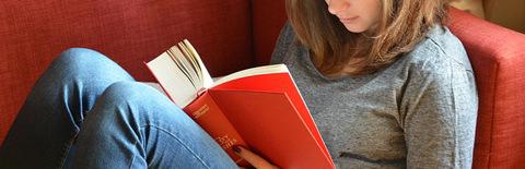 窓際で本を読む女性の写真