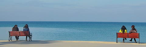 海辺に佇む2つのベンチの写真