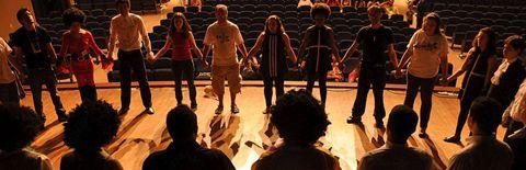 ステージ上で輪になる若者たちの写真