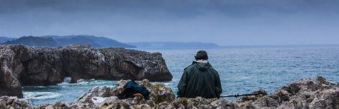 暗い海の見える岩場に座っている人の写真