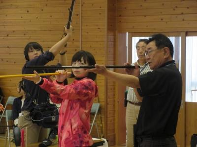 高橋キャスターが大福支部長からスポーツ吹矢の吹き方を教えてもらわれた後、実際に的に向かって吹矢を吹いて見られました。