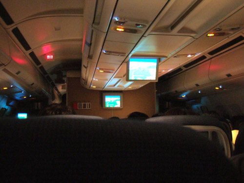 成田空港発(NRT)スカンジナビア航空Scandinavian Airlines - SAS Airbusエアバス A340-313X OY-KBI SK984便デンマークコペンハーゲン空港(CPH)行き。窓の日よけ窓のシェードが閉じられ照明が消された機内は暗い