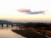 空がほんのり色づく、鉄橋を渡る貨物列車