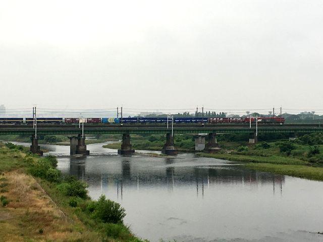 梅雨空をバックに貨物列車が川を渡る