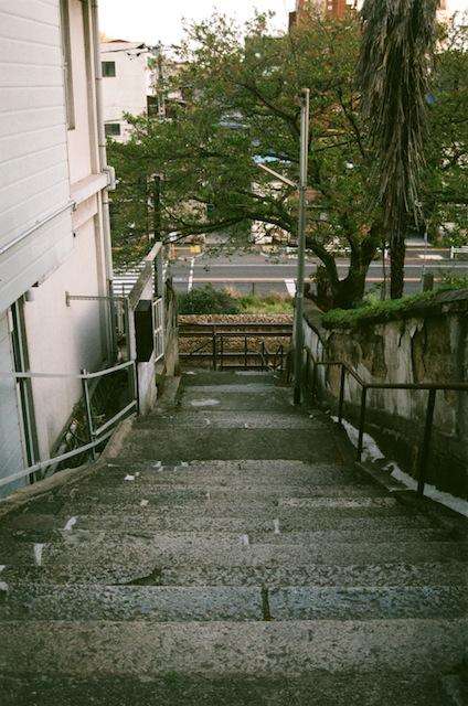 nalblog.com nalブログ。写真と旅と言葉たち 尾道散策 フィルム現像しました。  4月に尾道をフィルムで散策、ようやく現像フィルムが届きました。 日が落ち始める頃に散策開始、坂道の街尾道をフィルムカメラと共にさんぽしました。 出来上がりは、上々^^  現像したものをデータ化しましたので、ご紹介したいと思います。   それでは、散策スタート!入り組んだ狭い道を通って階段をのぼります。お店の入り口に猫発見。コチラを少し警戒しながら外の様子を観察しているようです。パトロール完了!大きく伸びをしたあとでゆっくりとお店に戻っていきました。ご苦労様です。     猫は数匹見たものの、夕刻だからか人通りはとても少なかったです。遠くでカップルが歩いているのを見た意外には西光寺から坂道を下る時に2・3人に会ったくらいです。出会う人の数と猫の数があまり変わらないって、やっぱり尾道は猫の町なんですね。お寺に寄り道 立派な松の木と幹の平らな部分を陣取ってコチラを見つめる黒猫さん お寺を通してもらい更に上に上っていきます。坂道をひたすら歩き、見晴らしのいいところへ 展望台は見晴らしがとてもよく、港の様子や町の様子、遠くの車の行き交いまで見ることができました。空が優しく染まり始めます。坂の町、尾道        フィルムがISO100だったものの、夕刻の優しい色合いが出た作品になりました。   松の木の上のネコさんはなかなかおしいです。 屋根まで写れば良かったのですが、あと30cm背が必要でした。   撮影1時間のうちに筆者が見た猫の数は3匹。 この尾道の町を半日散策したら、一体何匹の猫さんに出会えるのでしょうか? ワクワクしますね(。・ω・)♪  フィルムで町散策、クセになります!       写真:©2016 Yuko Yamada. All Rights Reserved 撮影地:広島県尾道市 フィルムカメラ:ミノルタα303si フィルム:FUJICOLOR100 三脚使用:なし 当ブログに掲載されている画像等の無断転載はご遠慮ください。