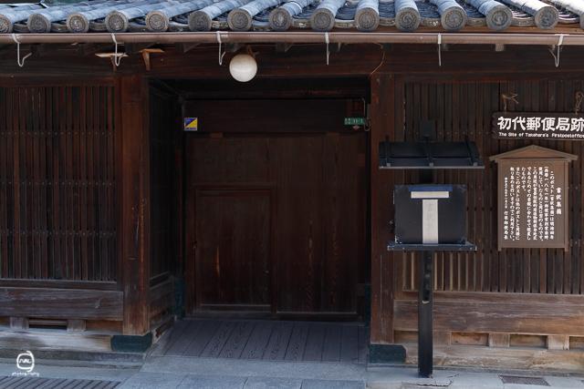 nalブログ。写真と旅と言葉たち nalblog.com  広島駅発、竹原市の町並みと海辺の景色 早朝広島駅を出発、広島県竹原市へと向かいます。今回は竹原の町並み保存地区とインターネットで見つけたフェリーで瀬戸内海を往復する「のとっこクルーズ」をするのが目的です。広島駅南口、Cホーム13番でバスを待ちます。7時11分、オレンジと青のラインが入った芸陽バスかぐや姫号に乗り込みます。  目立った渋滞もなくおよそ1時間で竹原に着きました。  町並み保存地区へは道の駅前のバス停で降りて歩いて向かいます。朝のコントラストの強い光は全景を撮るのには向きませんでしたが、建物のディテールが際立ってそれはそれで味がありました。「防火用水」西方寺の階段を登ったとこからの眺め壁や柱の質感や材質を見てみると、古いというよりは、逆にモダンな印象を受けました。黒い郵便ポスト。およそ150年前のポストと同じ型のものだそうです。 当時は書状集箱と言われていて、色も黒で屋根までついていたんですね。散策開始が8時半すぎ、日はもうとっくに登っていて、他の観光客もちらほら見かけました。  散歩中の紳士と「やっぱり夜明けがいいよね」と話しましたが、全景を撮るならやはり光の均一な夜明けか曇りの日、夕方日が沈んですぐかなぁと思いました。夜明けと夕暮れの空の色が入ると、さらに雰囲気が出そうな気がします。歴史のある建物を堪能し、道の駅に戻ります。竹原港旅客ターミナルは海の駅になっていて、道の駅と海の駅の間を無料送迎バスが走っています。バスに乗っても良かったのですが、せっかくなので歩いて向かいました。途中鳥居の大きな神社に寄り、旅の安全を祈願。綺麗な山に囲まれた綺麗な神社でした。歩くこと20分少々、海の駅に到着。目の前には青い海が広がっています。ターミナル横のウッドデッキには、竹原を舞台にしたアニメ「たまゆら」のキャラクターパネルが設置されており、 海をバックに記念撮影もすることができます。他にもたまゆらのラッピングフェリーやバスも走っていました。   ちょうど太陽が真上のころだったので、海の青がひときわ青く見えました。切符売り場でのっとこクルーズのことを尋ねてみると、行き先は何箇所かあるようで、とりあえず大崎上島の白水と竹原を往復する500円の往復切符を購入しフェリーに乗り込みました。乗るのは通常のフェリーですが、途中下船せず乗船港まで戻ってくるというのが条件で運賃が安くなるシステムのようです。   通常は乗りっぱなしなのですが、この日その時間にクルーズを利用したのは筆者一人だけだったようで、昼休憩に入るからという事で白水で下船し、竹原に向かうフェリーに再度乗り換える事となりました。往復で1時間ほどのクルーズですが、あっという間の時間でした。青い海、緑の島、水面に浮かぶ漁船、のどかな瀬戸内海の風景を堪能。竹原〜白水(しらみず)の他の竹原港発着のクルーズは、竹原〜垂水(たるみ)、高速船で1時間半ほどの竹原〜大長があります。 時間の遅い便に乗れば海から夕日が眺められ、時間によって印象が変わる瀬戸内海の風景をワンコインで船上から楽しめるなんてコスパのいいサービスでしょうか。次回来た時は、高速船に乗ってみたいと思います。   ちょうどいい時間になったので、海の駅でお昼をとることにしました。   海の駅3階にあるブルーバードでペペロンチーノとドリンクバーを注文。窓際で海を眺めながらゆったり過ごしました。   で、このあと事件が……。   バスの出発まで時間があったので、海の駅から歩いて15分くらいのところに的場海水浴場というビーチに向かいました。  ビーチがあって波止場があって、ちょうどいいアングルで瀬戸内海の島々を背景に船が行き来する様子を一望できたので、三脚を準備してカメラをセットしてポイントに移って撮影をしようと立ち上がったら、やってしまいました。  カバンから転げ落ちた24mmの単焦点レンズ、地面に落ちた音がコツン、そこでレンズキャップが外れたものの、勢いを失うことなく転がり続けるレンズとキャップ……岩場の斜面も器用に転がり続け、浅瀬に華麗なダイブを決めました。  購入して1ヶ月、あぁ…  とりあえず三脚をポイントに設置してから、5分くらい間を置いて浅瀬に入りレンズを拾いあげました。本体に取り付ける部分には水が入っていないようだったので、なんとか使えそうではありますが、フォーカスリングの部分に砂が入り込んだようで、MFは使えなくなりました。翌日動作テストをしたところ、AFは動くけど、MFは使えないという不思議な状態になっていました。レンズ内に水が入り込んだ様子もなく、撮影した画像を見ても問題ない様子。修理費用が本体価格とあまり変わらず、今は買い換える余裕もないので、完全に使えな