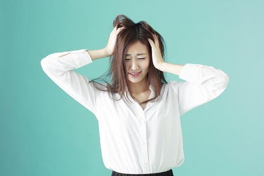 髪をかきむしって悩む若い女性